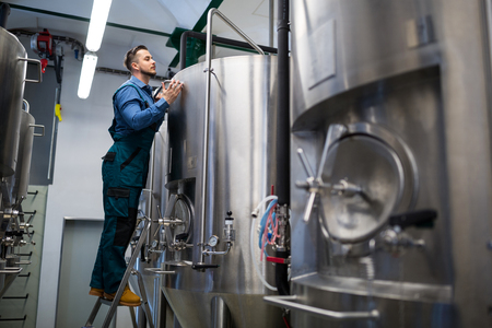 attentive: Attentive maintained worker working at brewery Stock Photo