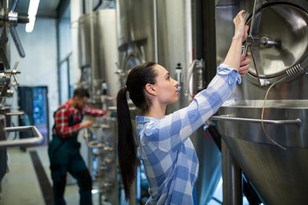 brewery: Female maintenance worker examining brewery machine at brewery