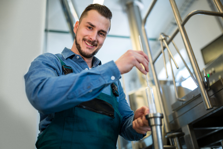 brewer: Happy brewer checking beer with hydrometer at brewery