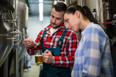 brewers: Brewers testing beer with litmus paper at brewery Stock Photo