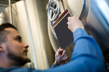brewery: Maintenance worker writing on notepad at brewery Stock Photo