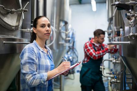 brewery: Female maintenance worker testing brewery machine at brewery
