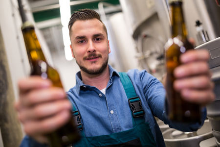 brewer: Portrait of handsome brewer holding two beer bottle at brewery