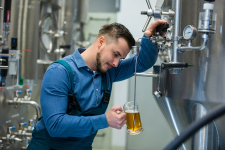 attentive: Attentive brewer testing beer at brewery
