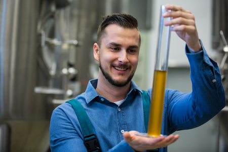 brewery: Happy brewer hydrometer cylinder at brewery