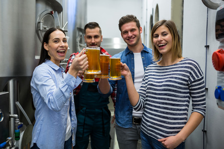 brewers: Portrait of happy brewers toasting beers at brewery