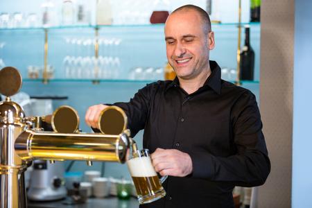 beer pump: Bar tender filling beer from bar pump at bar counter Stock Photo