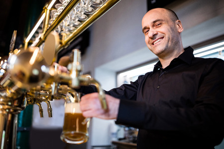 brewer: Portrait of smiling brewer filling beer in beer glass from beer pump in bar