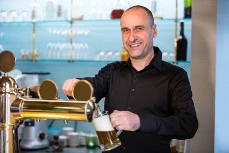 Retrato de barman llenado de cerveza de la bomba de barra en barra de bar