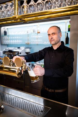 beer pump: Portrait of brewer filling beer in beer glass from beer pump in bar Stock Photo