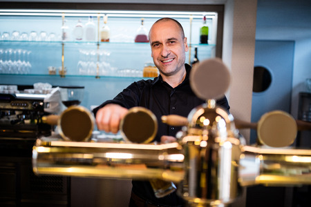 mature business man: Portrait of smiling brewer filling beer in beer glass from beer pump in bar