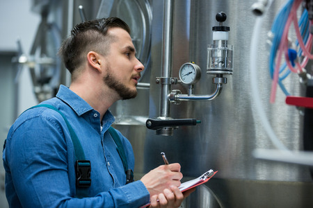 attentive: Attentive maintenance worker writing on clipboard at brewery Stock Photo