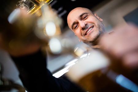 beer pump: Portrait of smiling brewer filling beer in beer glass from beer pump in bar