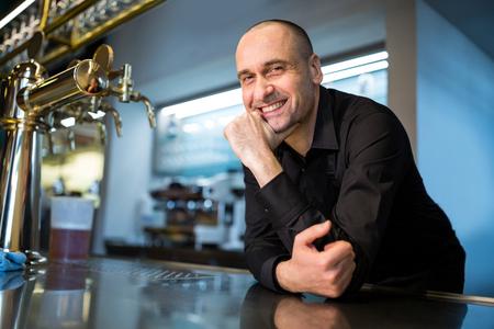 Retrato de barman feliz apoyado en la barra del bar