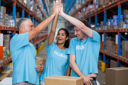 clapping hands: Happy volunteers are clapping hands each other in a warehouse