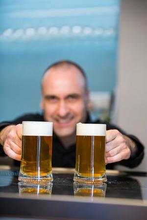 tender: Bar tender offering beer at bar