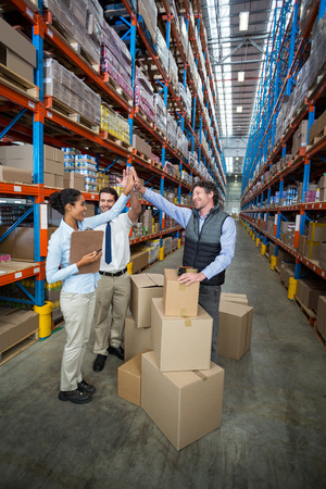 manos aplaudiendo: Happy managers are clapping hands each other in a warehouse