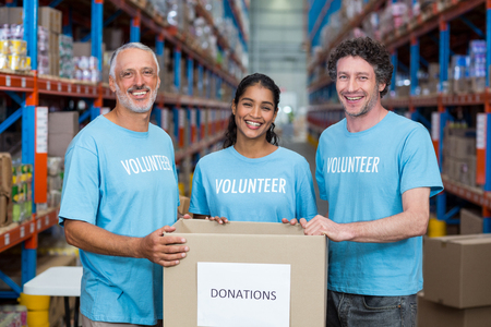 selfless: Happy volunteers are smiling and posing with a donations box in a warehouse Stock Photo