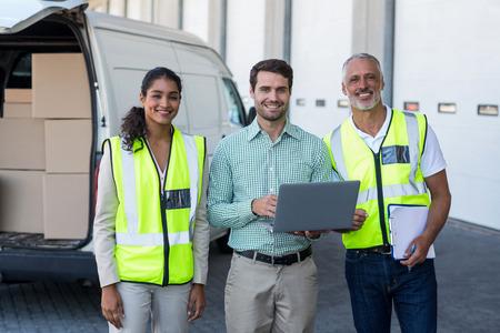 Manager et les travailleurs sont souriants et posant le visage à la caméra en face d'un entrepôt