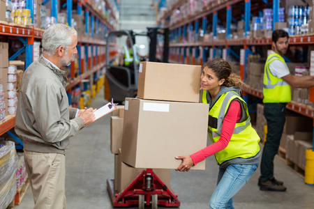 cajas de carton: Worker holding cardboard boxes looking her manager in a warehouse Foto de archivo