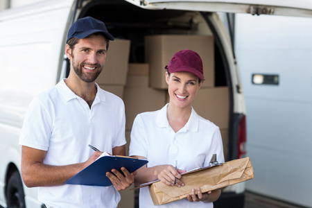 loading bay: Portrait of delivery people are holding goods and smiling to the camera in front of a wraehouse