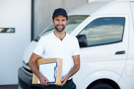 loading bay: Portrait of delivery man is holding cardboard box and posing in front of a warehouse