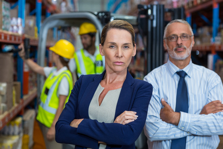 Serious managers are posing with crossed arms in warehouse