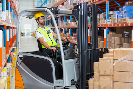 pallet truck: Worker is driving a pallet truck in a warehouse