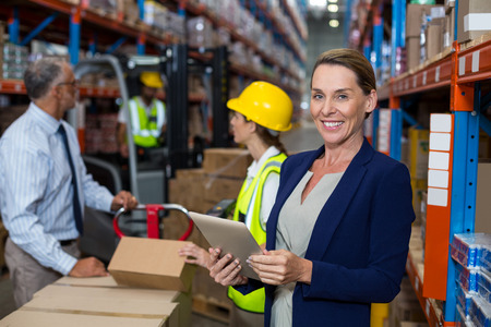 Business woman standing in front warehouse worker in warehouse Stock Photo