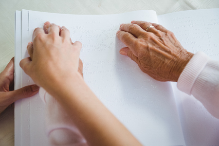 braille: Nurse helping senior woman with braille in a retirement home