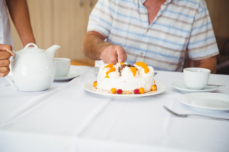 retirement home: Patient is cutting the cake in a retirement home Stock Photo