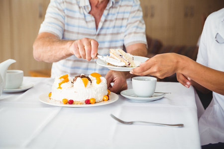 nurse home: Happy nurse serving a dessert to his patient in a retirement home