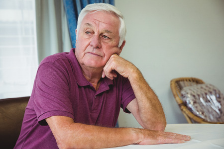 solitariness: Senior man sitting at a table in a retirement home Stock Photo