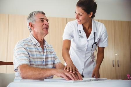 braile: Enfermera que ayuda a hombre mayor con braille en una casa de retiro