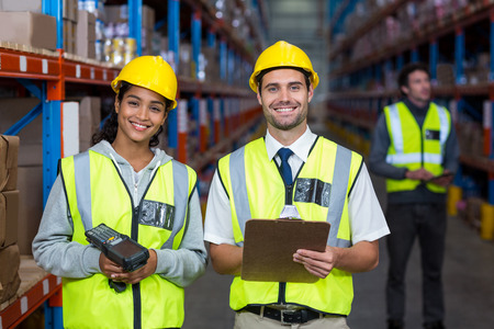 norms: Smiling worker wearing yellow safety vest looking at camera in warehouse Stock Photo