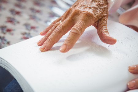 sheltered accommodation: Senior woman using braille to read in a retirement home Stock Photo