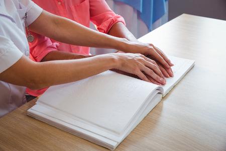 braile: Enfermera que ayuda a la mujer mayor con braille en una casa de retiro Foto de archivo