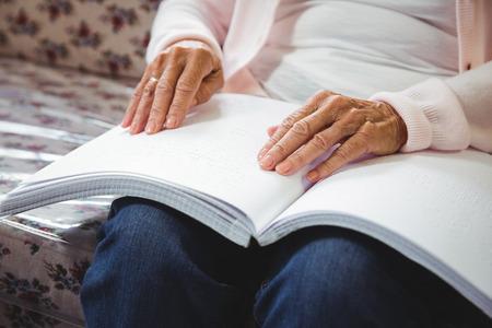 braille: Mujer mayor que usa braille para leer en una casa de retiro