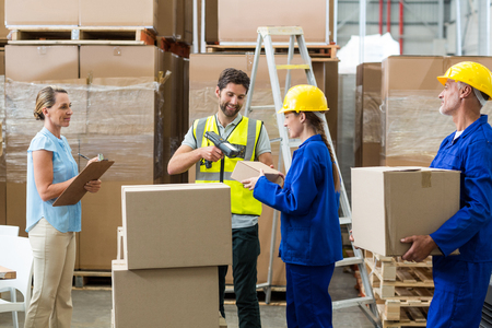 carrying: Workers carrying boxes in warehouse