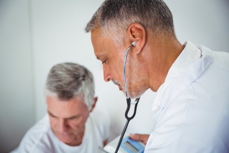 sheltered accommodation: Doctor using stethoscope in a retirement home Stock Photo