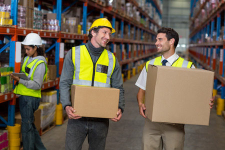 each other: Workers holding box looking each other in warehouse