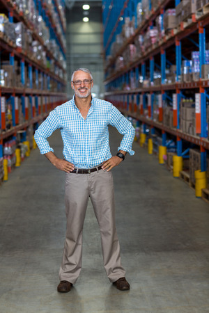 crossing arms: Smiling men crossing arms in warehouse