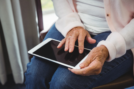 sheltered accommodation: Senior woman using a digital tablet in a retirement home Stock Photo