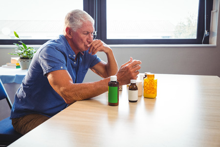 sheltered accommodation: Senior man holding medicine in a retirement home
