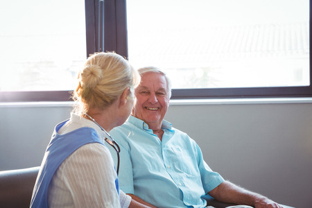 sheltered accommodation: Nurse and senior man sitting on sofa in a retirement home