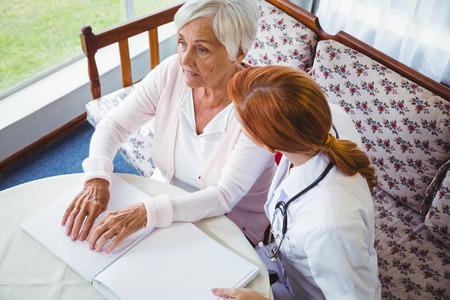 braille: Enfermera que ayuda a la mujer mayor con braille en una casa de retiro Foto de archivo