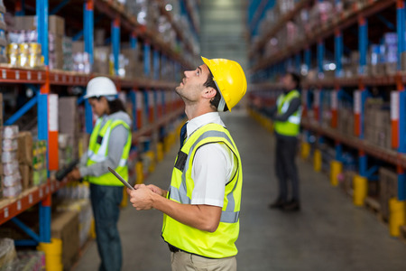 norms: Worker with yellow safety vest looking up in warehouse Stock Photo