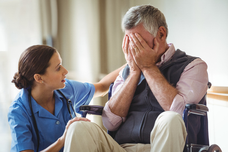 sad lady: Nurse taking care of sad senior man in a retirement home