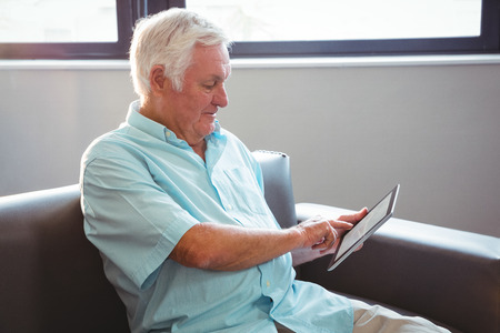 sheltered accommodation: Senior man using a digital tablet in a retirement home