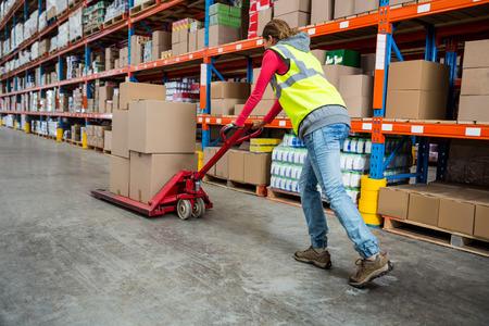 empujando: Trabajador que empuja la carretilla con cajas en almac�n
